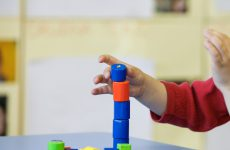 Child playing with homemade, do-it-yourself educational toys, stacking and arranging colorful pieces. Learning through experience concept, gross and fine motor skills, educational approach concept.